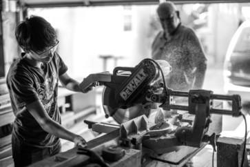 Boy using compound sliding miter saw