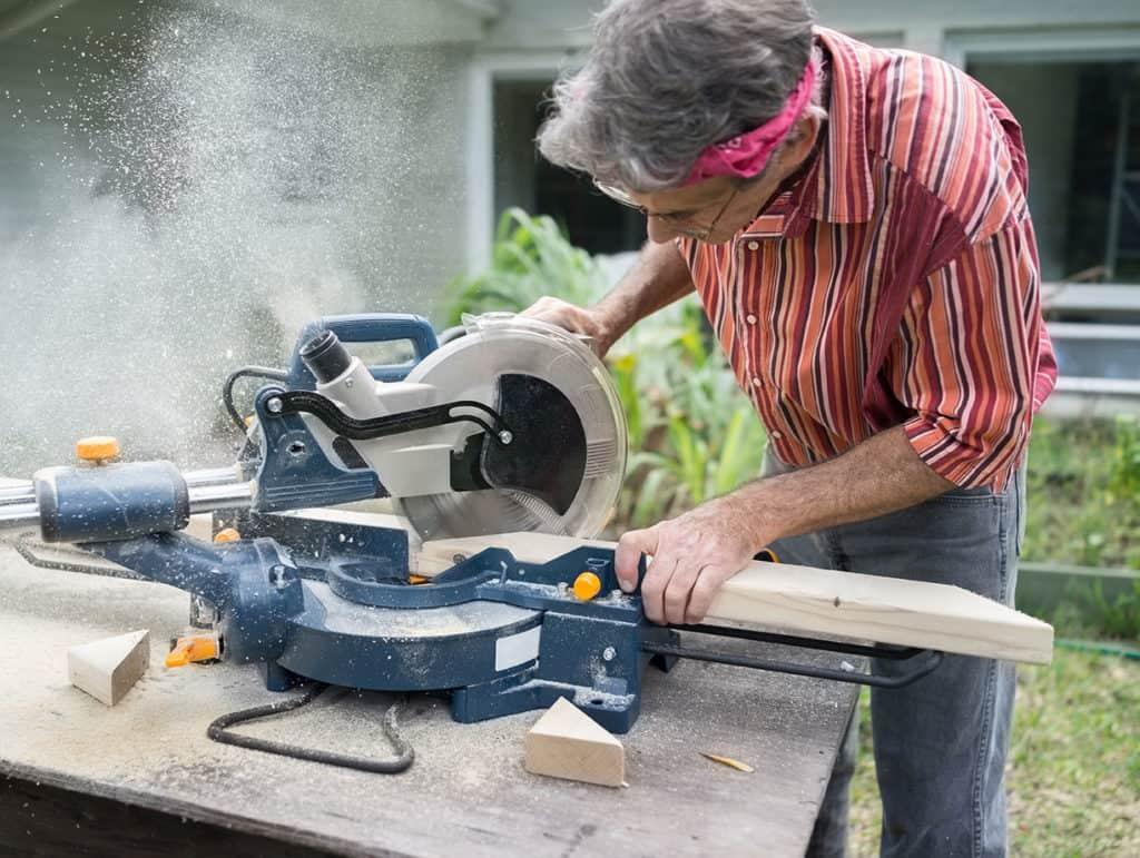 Carpenter mitering lumber on sliding miter saw