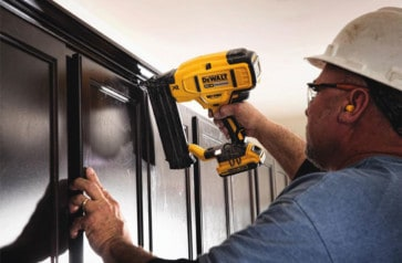 Battery operated brad nailer from Dewalt installing trim above cabinets