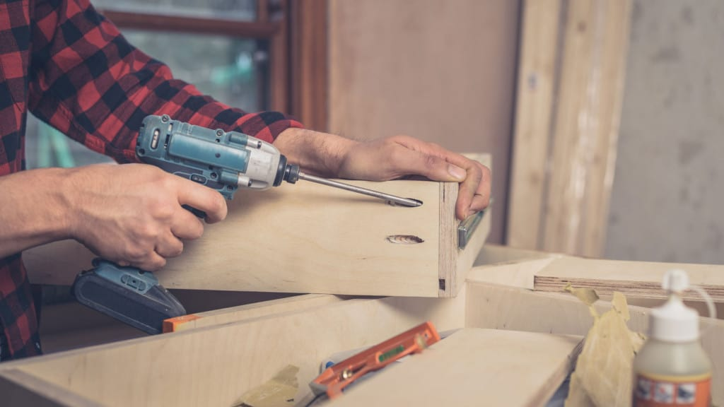 Carpenter using impact driver to assemble cabinet