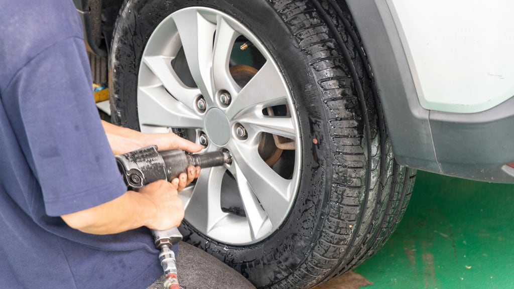 Lug nut on tire being removed by air impact wrench