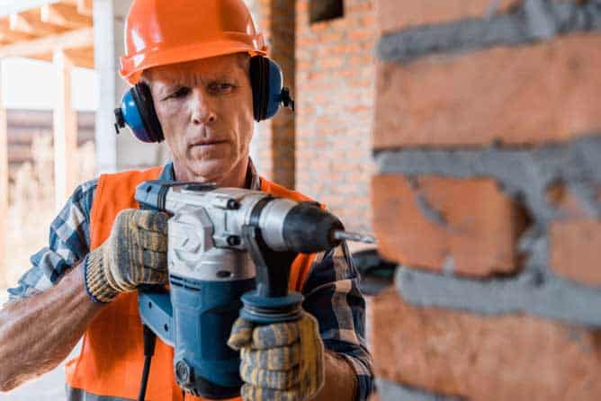 Construction worker using a Makita hammer drill on a brick wall