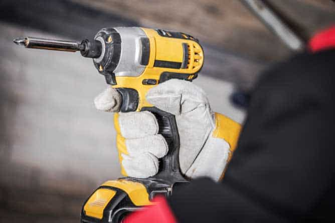 Man holding yellow Dewalt impact driver with a phillips screwdriver bit