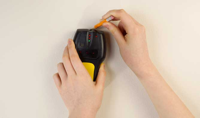 Woman using pencil to mark stud location identified by an electronic stud finder