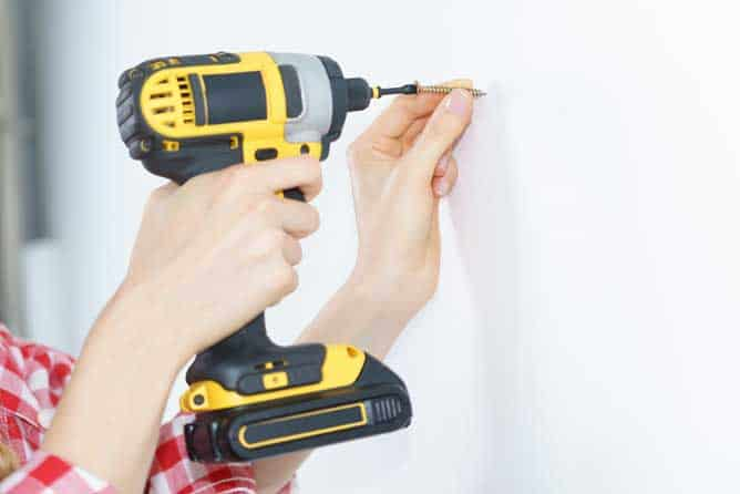 Woman using a cordless Dewalt impact driver to drive a screw into drywall